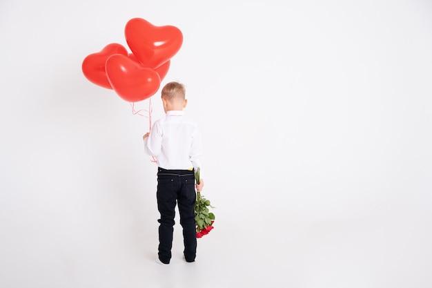 Ragazzo in tuta detiene bouquet di rose e palloncini cuore