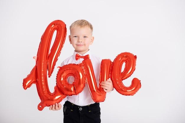 Ragazzo in giacca e cravatta a farfalla rossa tiene la scritta amore da palloncini su un muro bianco.