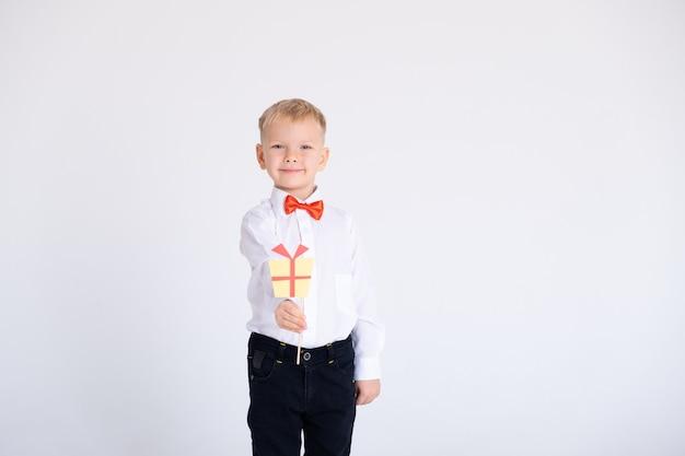 Ragazzo in giacca e cravatta a farfalla rossa tiene il disegno del regalo di toppers o stikcers su un muro bianco.