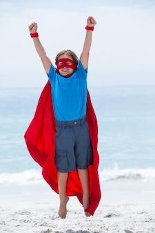 Ragazzo in costume da supereroe che salta con le braccia alzate