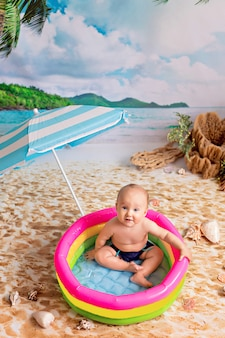 Ragazzo che nuota in una piscina gonfiabile sotto l'ombrellone sulla spiaggia di sabbia con palme in riva al mare