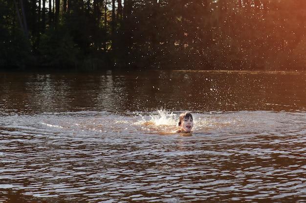 Ragazzo che nuota e sguazza nell'acqua ondulata del fiume, del mare o del lago nelle calde giornate estive
