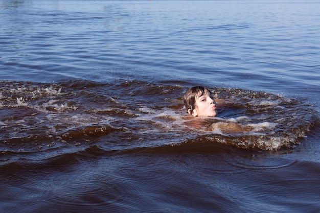 Ragazzo che nuota nell'acqua blu ondulata del fiume, del mare o del lago in una giornata di sole.