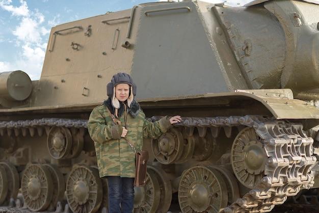 Un ragazzo in uniforme da petroliera vicino a un carro armato in inverno in tempo di pace in russia in vacanza