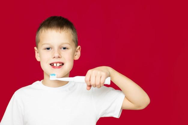 Ragazzo adolescente 7-10 in una maglietta bianca con uno spazzolino elettrico bianco e dentifricio si lava i denti su uno sfondo rosso