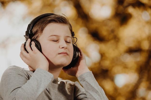 Adolescente del ragazzo che ascolta musica rilassante in una foresta durante una bella giornata di sole, relax, atto di meditazione
