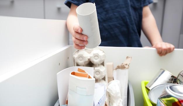 Ragazzo che getta la spazzatura in uno dei quattro diversi bidoni per lo smistamento dei rifiuti