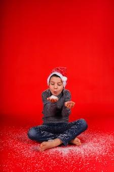 Il bambino ragazzo soffia la neve artificiale dalla sua mano su uno sfondo rosso