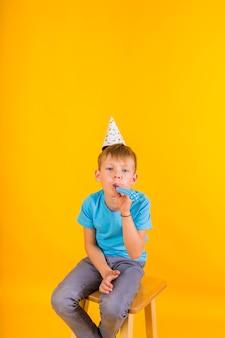 Il bambino si siede in un berretto da festa di carta e suona un fischio su uno sfondo giallo