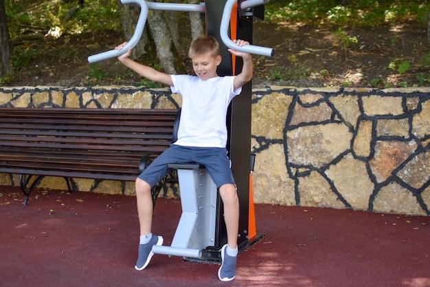 Ragazzo si allena sul simulatore di sport all'aria aperta. bambino di sport in estate nel parco giochi.