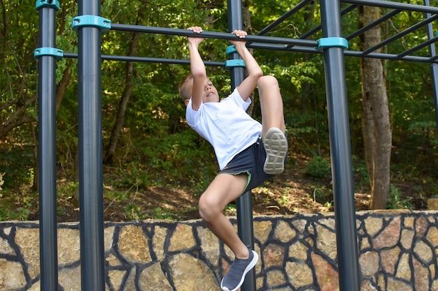 Ragazzo si allena sul simulatore di sport. esercizi ginnici. ragazzo superando gli sforzi.