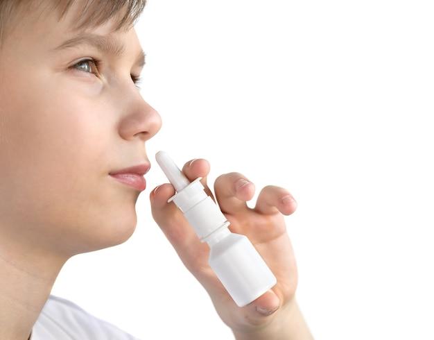 Un ragazzo di dodici anni spruzza spray nasale isolato. adolescente che utilizza spray nasale.