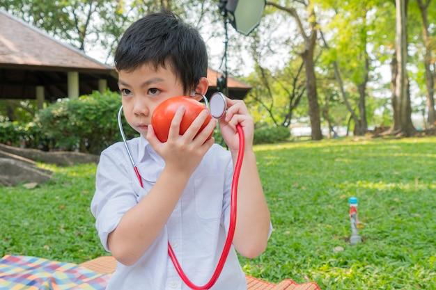 Il ragazzo usa gli stetoscopi e gioca con il simbolo del pomodoro della frutta