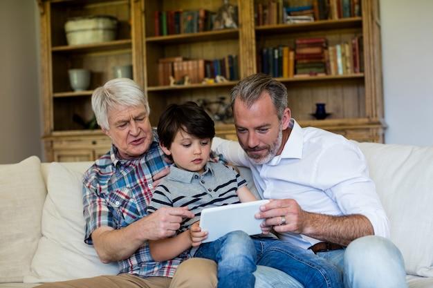 Ragazzo che utilizza compressa digitale con suo padre e suo nonno nel salone