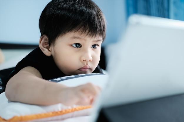 Un ragazzo che utilizza un tablet pc a casa in camera da letto.