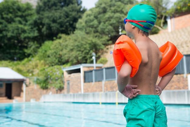 Ragazzo che indossa fascia da braccio in piedi a bordo piscina