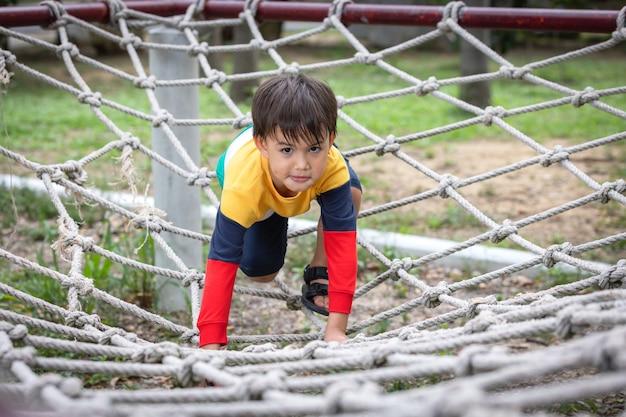 Un ragazzo che indossa abiti dai colori vivaci che si arrampica sul telaio della corda nel parco giochi