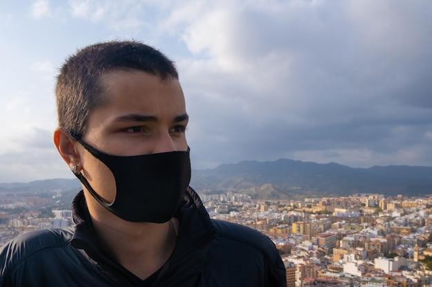 Ragazzo che indossa la maschera facciale guardando la città di malaga dall'alto in spagna.