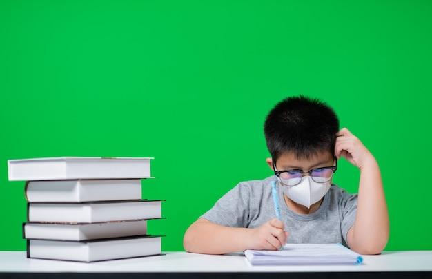 Ragazzo che indossa la maschera protettiva e fa i compiti su schermo verde, carta da lettere per bambini, concetto di educazione, torna a scuola