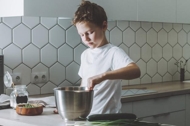 Il ragazzo frusta l'omelette con la frusta