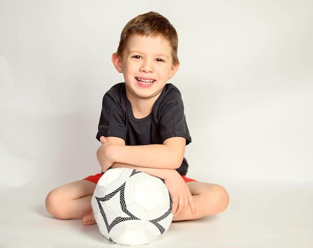 Un ragazzo su uno sfondo bianco. ragazzo bello sorridente che si siede su una priorità bassa bianca.