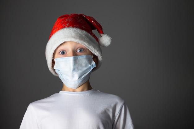 Ragazzo in una maglietta bianca, cappello di natale e mascherina medica su sfondo grigio.