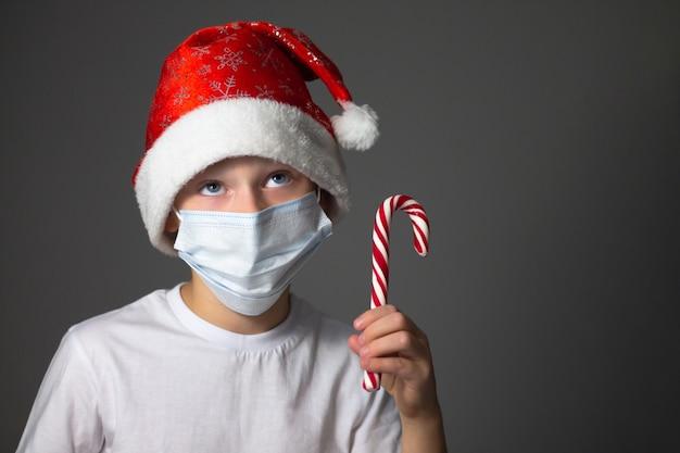 Ragazzo in una maglietta bianca, berretto di natale e mascherina medica che tiene lecca-lecca su grigio