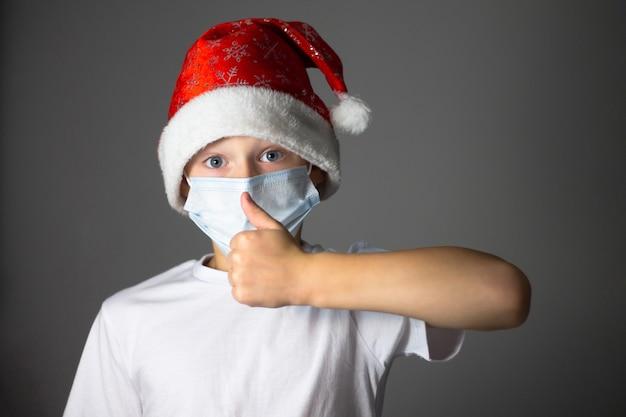 Ragazzo in una maglietta bianca, berretto natalizio e mascherina medica mostra un pollice in alto sul grigio