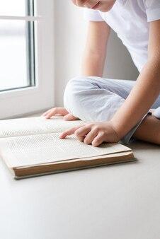Il ragazzo in una maglietta bianca legge un libro sul davanzale della finestra. luce dalla finestra