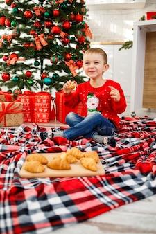Il ragazzo che si siede vicino all'albero di natale per il nuovo anno. decorazioni natalizie con regali, un bambino vicino all'albero di natale mangia croissant e sorride