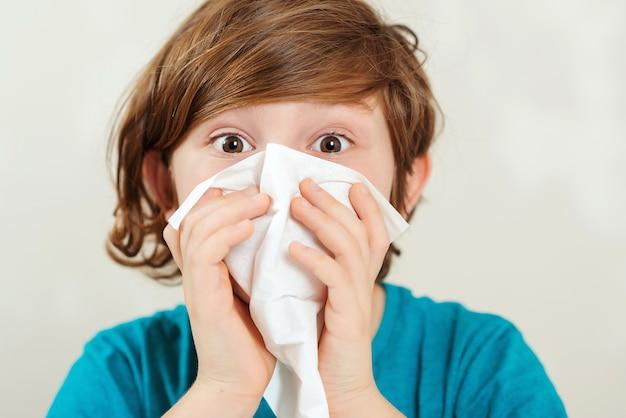 Il ragazzo pulisce un naso un tovagliolo. il bambino ha un virus, naso che cola e mal di testa.