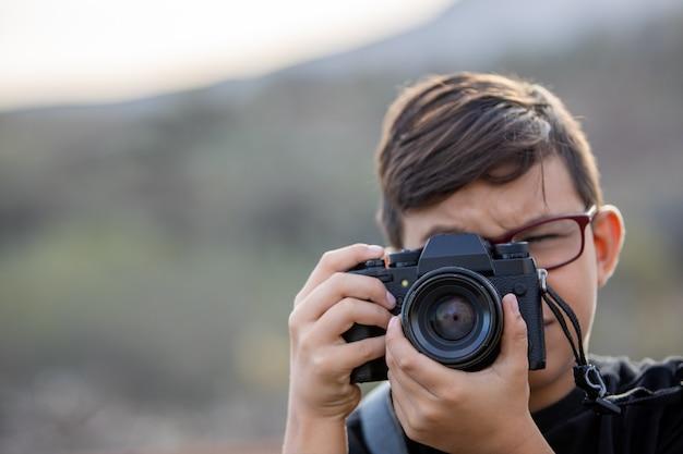 Ragazzo con la macchina fotografica che cattura foto