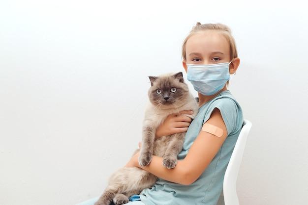 Ragazzo con gatto seduto alla sedia dopo il vaccino. bambino vaccinato contro l'infezione da coronavirus. bambino che indossa una maschera protettiva.