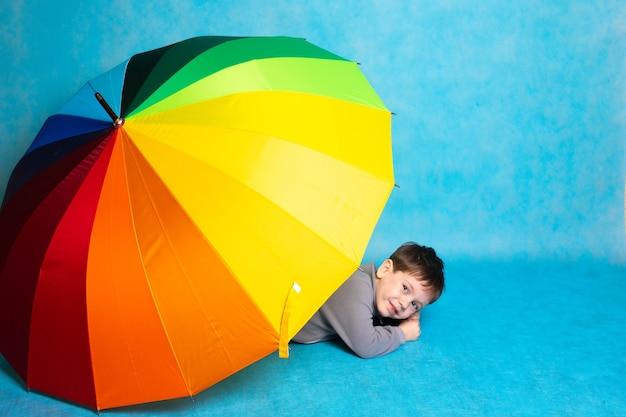 Un ragazzo con un ombrello colorato su sfondo blu