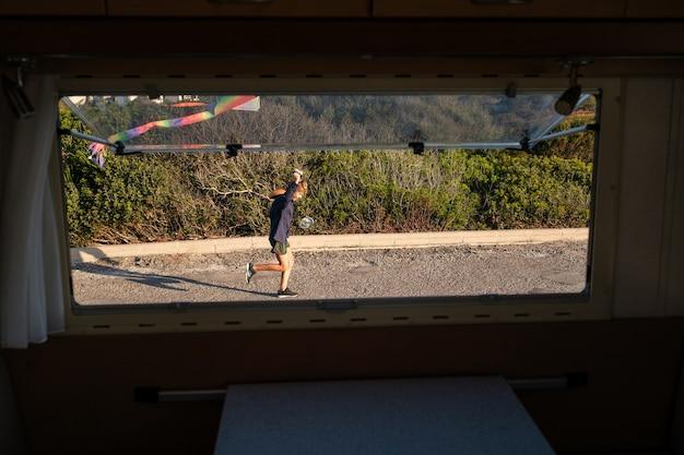 Ragazzo con un aquilone colorato che corre sul sentiero asfaltato dietro la finestra della roulotte durante il viaggio in estate