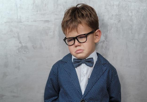 Ragazzo con gli occhiali su un muro grigio con l'emozione di risentimento e pianto
