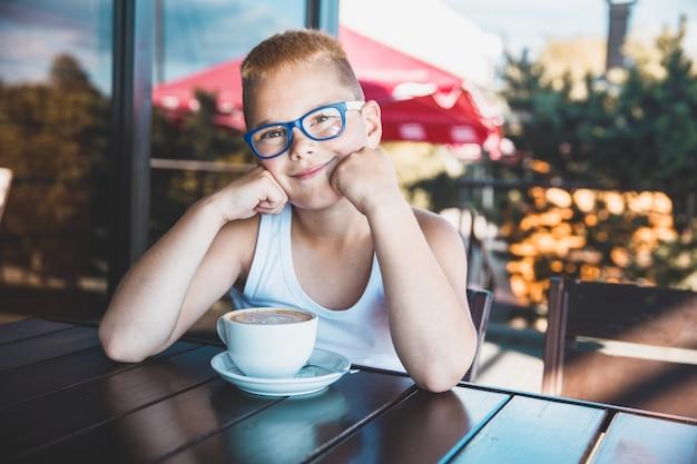 Ragazzo con gli occhiali in un ristorante a bere caffè