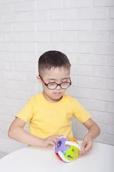 Un ragazzo con gli occhiali con sindrome di down si siede a un tavolo e gioca con i giocattoli
