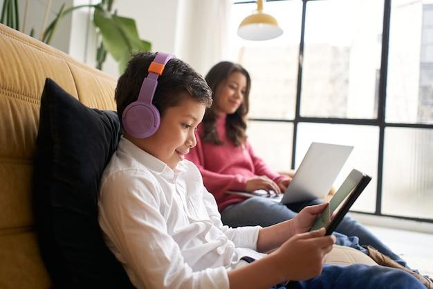 Ragazzo con le cuffie gioca con un tablet sul divano di casa mentre sua madre lavora a distanza su di lei...