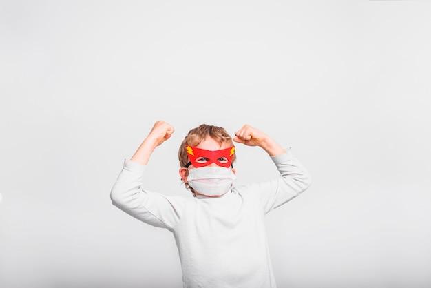 Ragazzo con maschera ospedaliera, malato di virus, vestito da supereroe, concetto di forza e speranza.