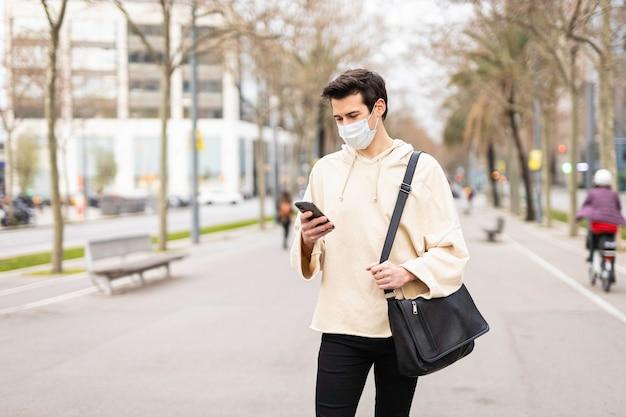 Ragazzo con telefono cellulare e maschera