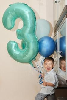 Ragazzo con il numero tre e i palloncini per il suo compleanno