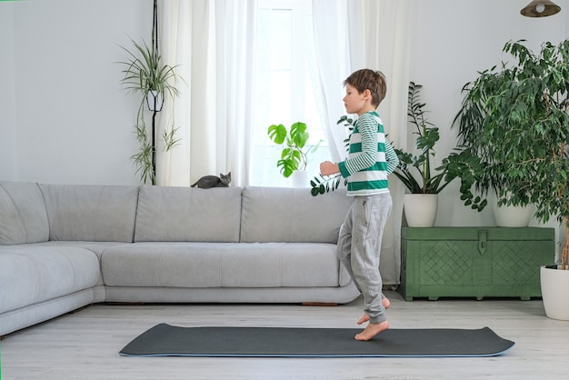 Il ragazzo con animale domestico va a fare sport a casa online. il bambino fa esercizi nella stanza.
