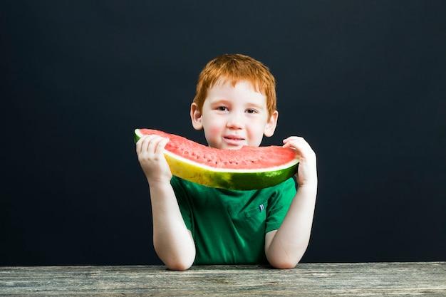 Il ragazzo con i capelli rossi mangia un'anguria rossa succosa tagliata a pezzi