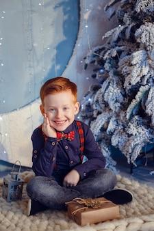 Un ragazzo con i capelli rossi e le lentiggini accanto all'albero di natale