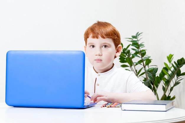 Un ragazzo con i capelli rossi impara a distanza tramite un computer e internet