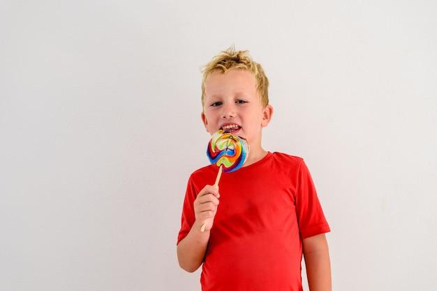 Ragazzo con la camicia rossa su fondo bianco che mangia un lecca-lecca divertimento variopinto e risata
