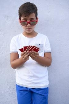 Ragazzo con occhiali da sole rossi che giocano a poker