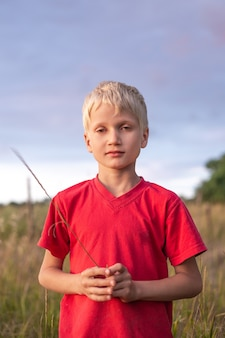 Un ragazzo con le lacrime agli occhi in una maglietta rossa sul campo in estate. la manifestazione di una reazione allergica, febbre da fieno sulla fioritura delle erbe.
