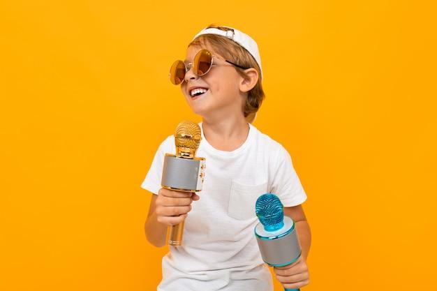 Ragazzo con due microfoni su una parete luminosa gialla